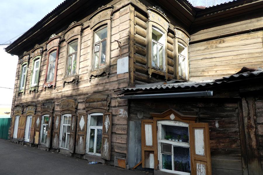 Maison typique de la région : architecture en bois, petits volets et belles corniches